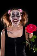 Insane funny female clown with red rose Stock Photos