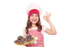 Happy little girl cook with chocolate donuts and ok hand sign Stock Photos