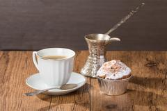 Cup of coffee with tasty muffins and turk for coffee Stock Photos