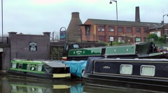 Old industrial bottle kiln building and canal barges Middleport Stock Footage