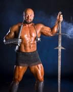 Handsome muscular ancient warrior with a sword Stock Photos