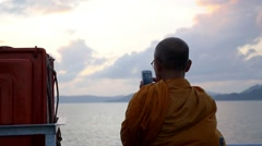 Buddhist Monk Using Phone and Shooting the Sea Stock Footage