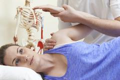 Male Osteopath Treating Female Patient With Shoulder Problem Stock Photos