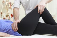 Male Osteopath Treating Female Patient With Hip Problem Stock Photos