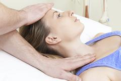 Male Osteopath Treating Female Patient With Neck Problem Stock Photos