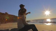 2 angles - two young people chat and enjoy the beach clear day sun Stock Footage