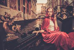 Beautiful woman in red cloak riding on gondola Stock Photos