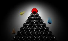 Red sphere on a pile of black spheres pushing down other spheres - stock photo
