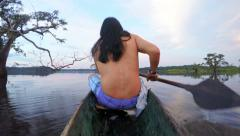 Indigenous men on wooden canoe, on board camera, shot from the back side of boat Stock Footage