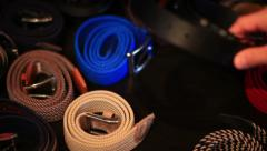 Man choosing one strap belt from various colors and models Stock Footage