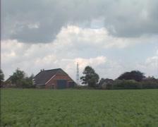 GRONINGEN, THE NETHERLANDS - 1980s: shed rural landscape + zoom out flare stack Stock Footage