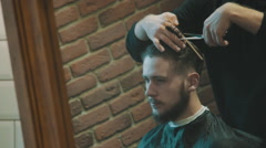 Barber cuts the hair of the client with scissors in mirror Stock Footage