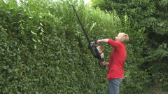 Woman trimming a hedge in garden Stock Footage
