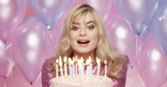 Beautiful young woman blowing out candles celebrating birthday pink and blue Stock Footage