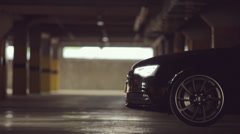 Black Audi leaves the parking lot with its lights on Stock Footage