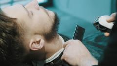 Barber shave the beard of the client with clipper - stock footage