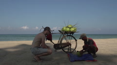 Ngwe Saung, Tourist looks at how man opens a coconut Stock Footage