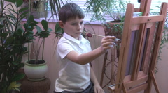 Boy draws a picture on the easel Stock Footage