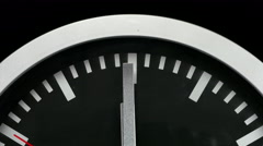 Black wall clock on black background, ticking the last seconds before twelve Stock Footage