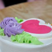 White creamy cake and violet flowers green leaf heart-shaped decorated with c - stock photo