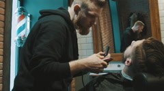 Barber shaves the beard of the client with trimmer Stock Footage