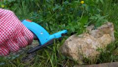 Cutting grass with a hand grass shears between rocks in a garden Stock Footage