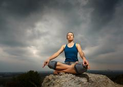Woman doing yoga against the setting sun - stock photo