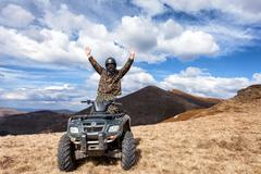 Male rider on ATV at mountain top Stock Photos