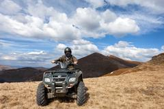 Male rider sitting on ATV at mountain top Stock Photos