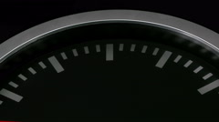 Black wall clock isolated on black background. Red second hand passing by Stock Footage