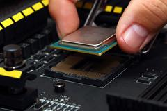 Installing central processor unit into motherboard - stock photo