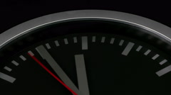 Black wall clock on black background, showing five minutes before midnight - stock footage