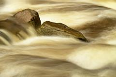 Big slippery boulders in mountain stream. Clear water blurred by long exposure, - stock photo