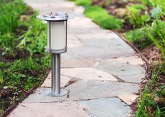 Solar-powered lamp on garden path. - stock photo
