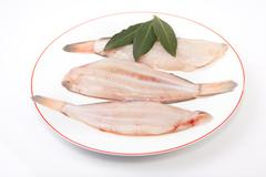 Raw sole fish with bay branch - stock photo