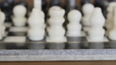 A dolly shot of marble chess pieces on a chess board Stock Footage