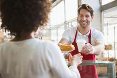 Smiling waiter giving lunch and hot drink to customer - stock photo