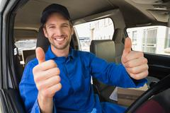 Stock Photo of Delivery driver smiling at camera in his van