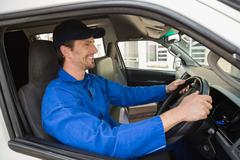 Stock Photo of Delivery driver smiling in his van