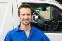 Smiling man in front of delivery van Stock Photos