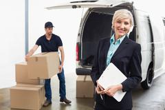 Delivery driver packing his van with manager smiling - stock photo