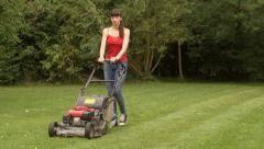 Woman mowing lawn Stock Footage