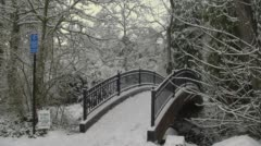 Snow covered arch bridge during winter, Lithia Park - stock footage