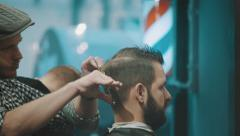 Barber cuts the hair of the client with scissors - stock footage