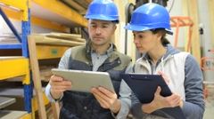Worker with overseer controling stock in warehouse Stock Footage