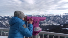 Young woman looking through telescope at viewpoint in the mountains HD Stock Footage