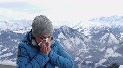 Young woman sneezes in winter mountains HD Stock Footage