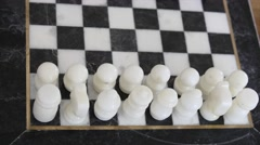 Chess pieces on the stone chess board Stock Footage