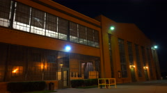 Lights glow inside a warehouse or factory at night. Stock Footage