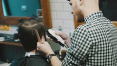 Barber cuts the hair of the client with clipper Stock Footage